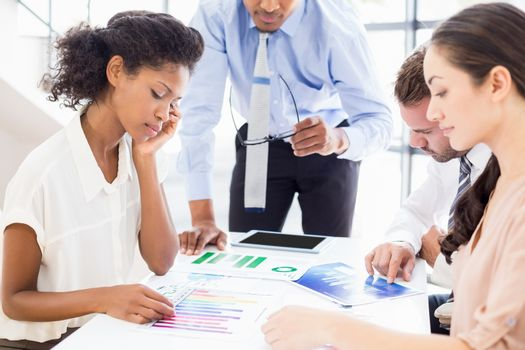 Businesspeople looking at reports in meeting