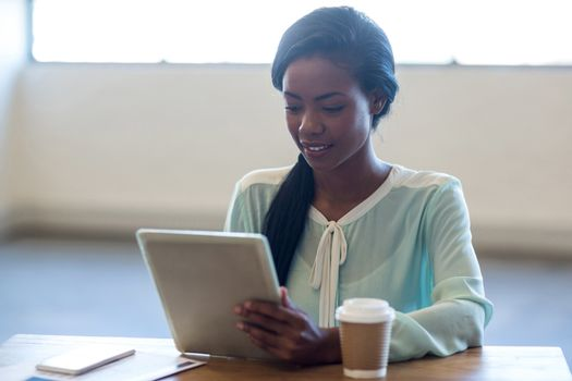 Businesswoman using digital tablet at her desk in the office