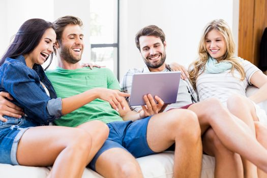 Friends are smiling and looking at a touchscreen at home