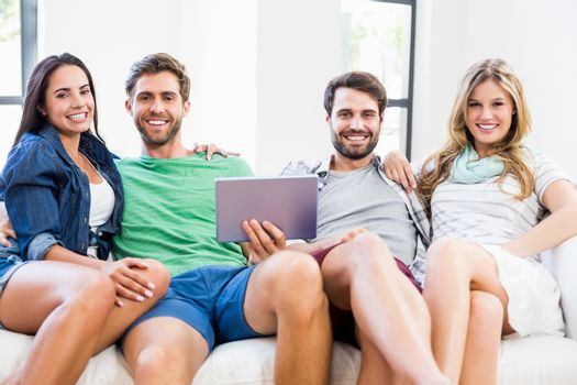 Portrait of happy friends sitting on sofa and using digital tablet at home