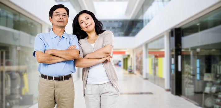Smiling couple with arms folded against interior of modern shopping mall