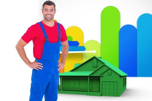 Composite image of happy handyman in overalls with hands on hip