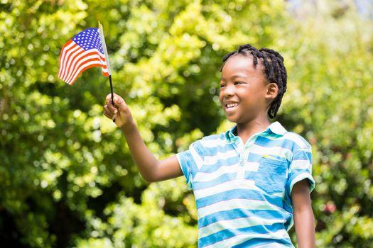 Smiling boy waving american flag