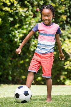 Smiling boy kicking the ball