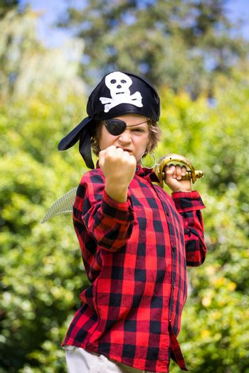 A kid with a costume of pirate is showing his strength