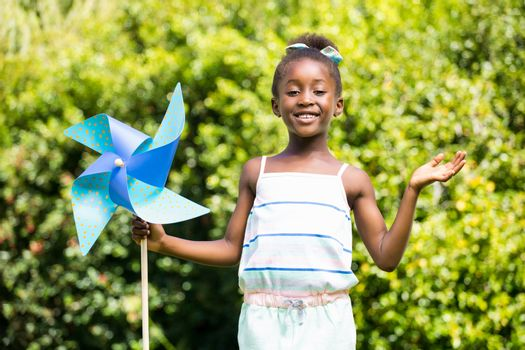Cute mixed-race girl smiling and holding a windmill