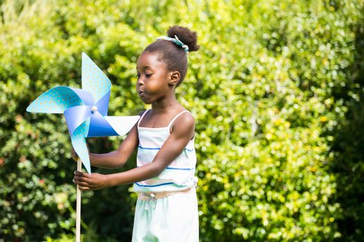 Cute mixed-race girl playing with a windmill