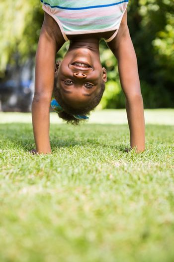 Portrait of a cute mixed-race girl smiling and doing a headstand