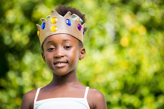 Portrait of a mixed-race girl smiling and wearing a crown