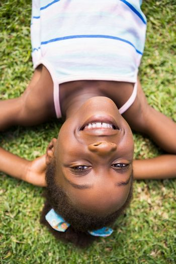 Portrait of a cute mixed-race smiling and lying on grass