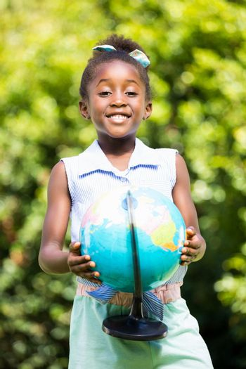 Cute mixed-race girl smiling and holding a globe