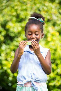 Cute mixed-race girl eating a watermelon