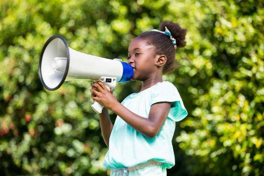 Cute mixed-race girl speaking on a megaphone