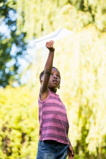 Cute mixed-race boy playing with a paper plane
