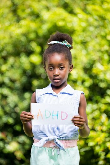 Cute mixed-race girl holding a paper with a message