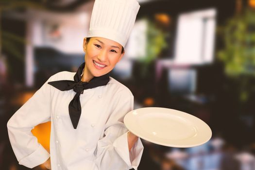 Smiling female cook holding empty plate in kitchen against restaurant interior