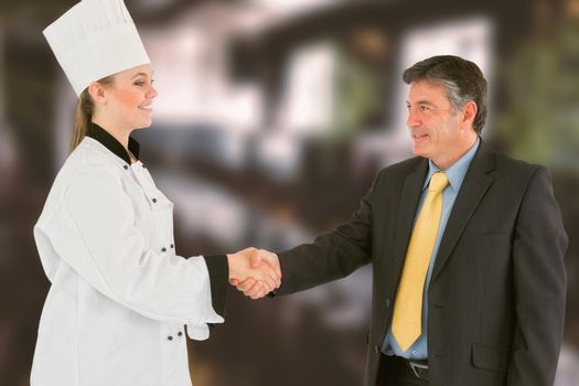 Businessman and female chef shaking hands against restaurant interior