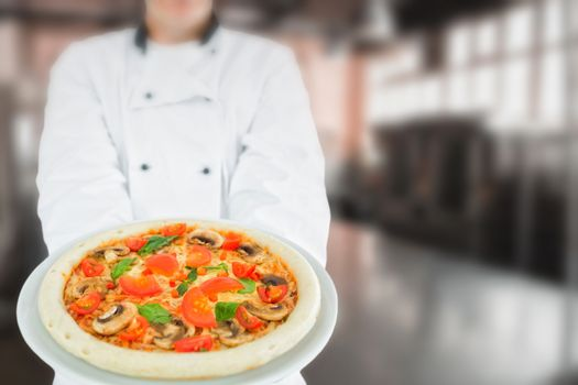 Chef holding delicious pizza against no one in the room