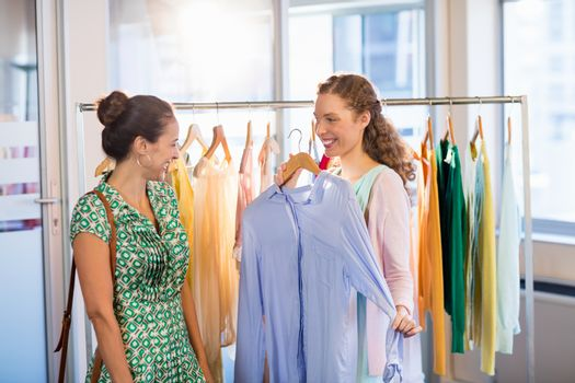 Woman selecting an apparel while shopping for clothes with her friend