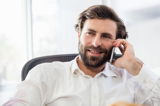 A smiling man passing a call