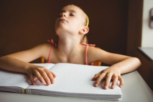 Blind girl using both hands to read braille