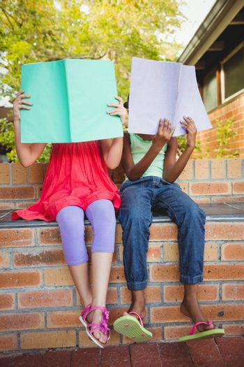 Two girls hided behind their copybook