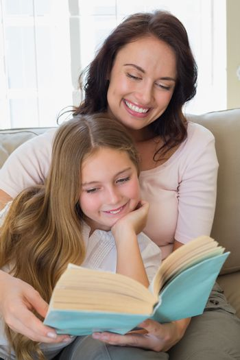 Woman and daughter reading story book