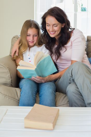 Girl and mother reading novel on sofa