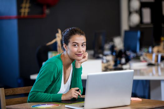 Businesswoman smiling at camera while seating at desk