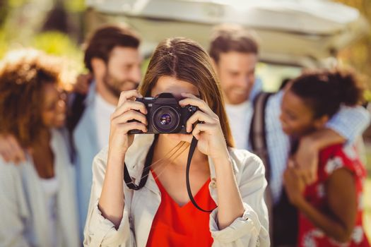 Woman clicking a photo from camera in park