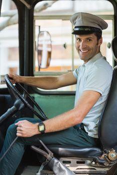 Portrait of smiling bus driver driving a bus