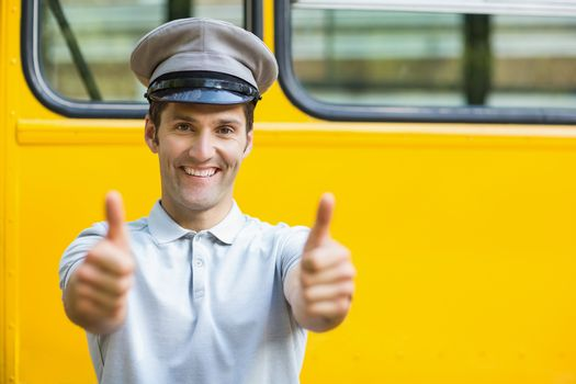 Portrait of smiling bus driver showing thumbs up in front of bus