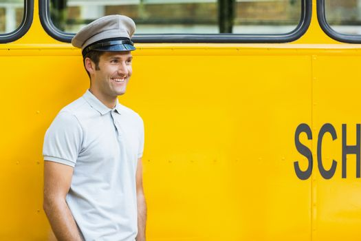 Bus driver looking away and smiling in front of bus