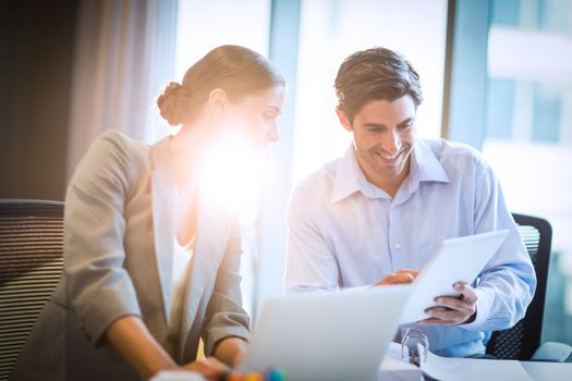 Businesswoman having a discussion with coworker on laptop