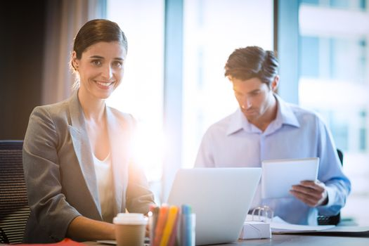 Businesswoman working on laptop with coworker