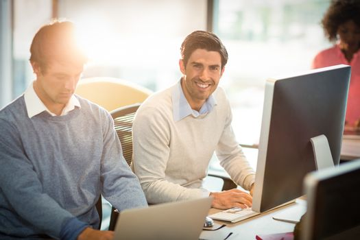 Man working on computer with coworker