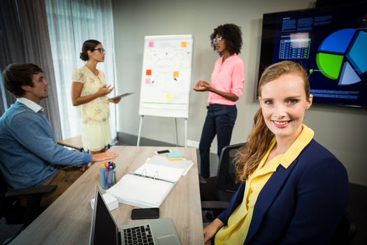 A colleague smiling at camera while coworkers discuss flowchart on whiteboard