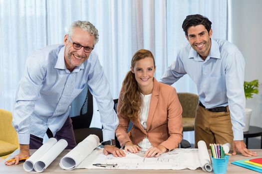 Businesswoman and coworker with blueprint on the desk