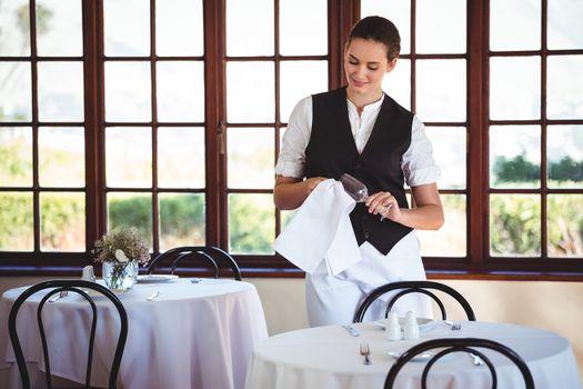 Waitress cleaning wineglass