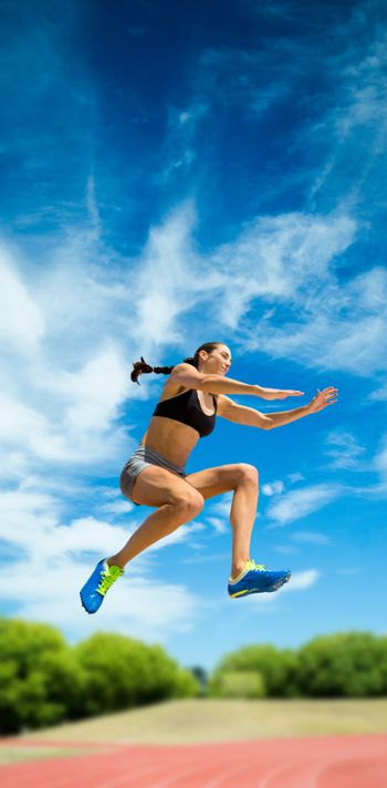 Sporty woman jumping against athletics field