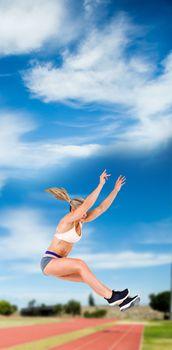 Female athlete jumping against athletics field
