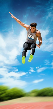 Sportsman jumping against athletics field