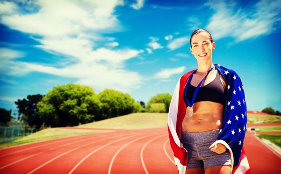Sporty woman posing and smiling with American flag against athletics field on a sunny day