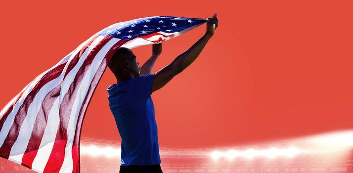 Rear view of sportsman raising an american flag