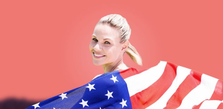 Composite image of sporty girl holding an american flag