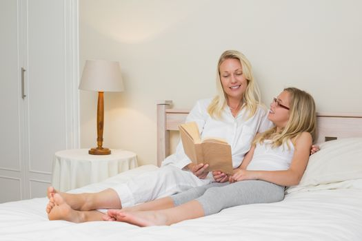 Mother and daughter with story book in bed