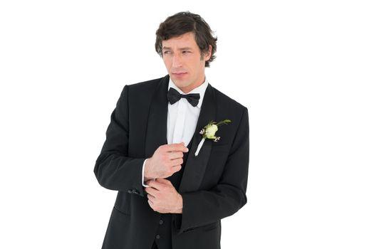 Groom in tuxedo adjusting cuff link