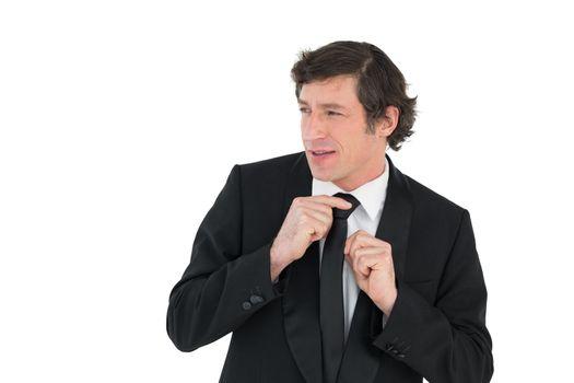 Groom adjusting necktie