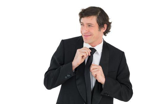 Happy groom adjusting necktie