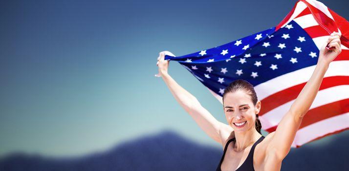 Portrait of happy sportswoman raising an american flag